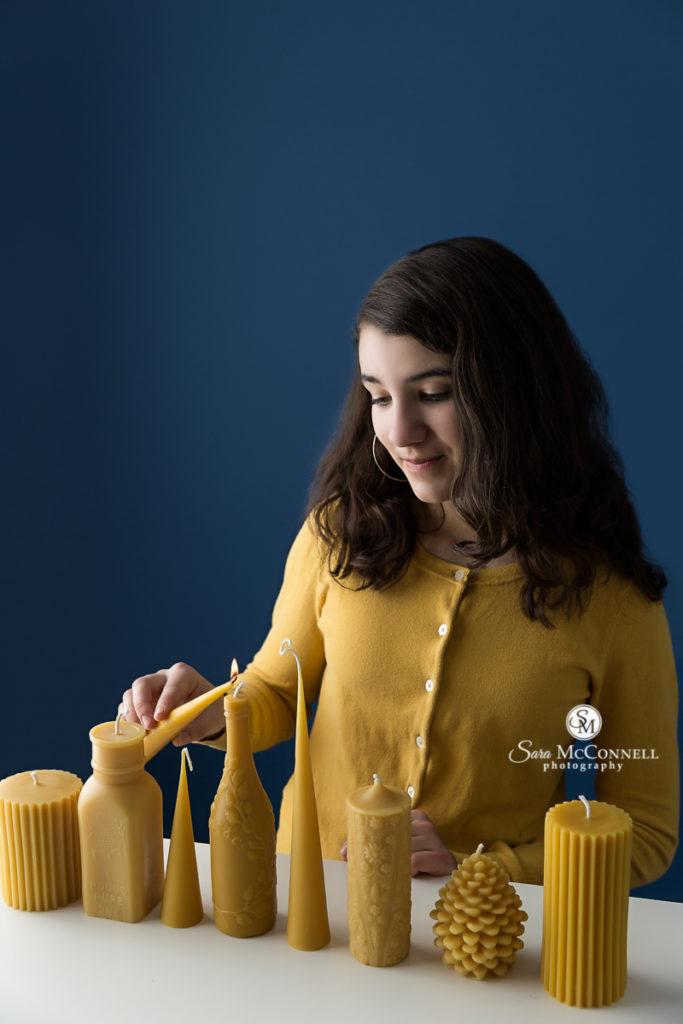 young girl lighting yellow candles