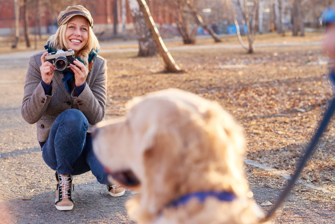 Smiling young woman holding photographic equipment and preparing to take photo of dog