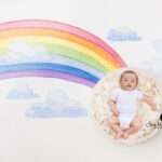 2 month old baby posed at the end of a rainbow